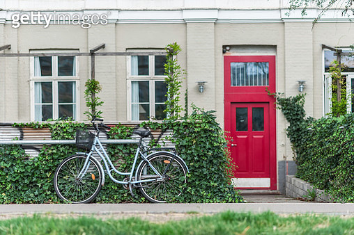 Cute bicycle on a quiet idyllic city street, vintage red front door in the background. - gettyimageskorea