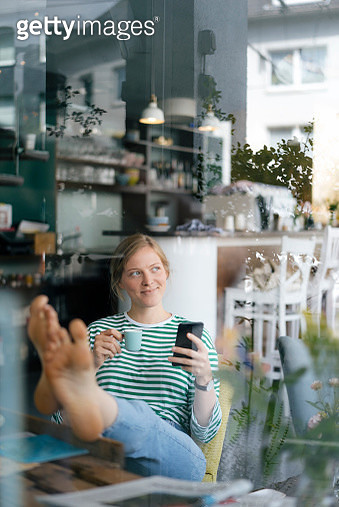 Smiling young woman with feet up holding cell phone and espresso cup in a cafe - gettyimageskorea