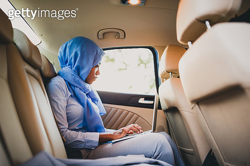 Muslim businesswoman, wearing hijab. She is on a business trip, using a laptop in a car - gettyimageskorea