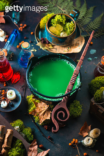Magical cauldron with a green potion in a cauldron, wooden wand, moss, candles, and crystals, witchcraft still life - gettyimageskorea