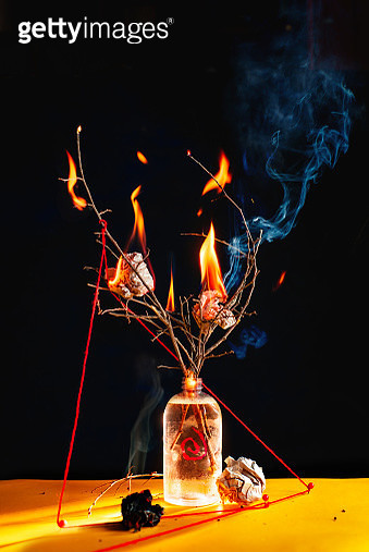 Plastic bottle with burning branches and crumpled paper balls, eco, and occult concept - gettyimageskorea