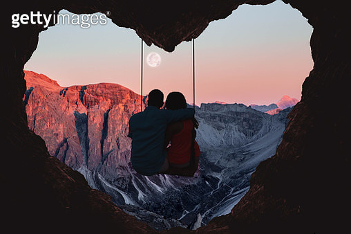 Couple on swing contemplating the mountains in a romantic view with heart shape. - gettyimageskorea