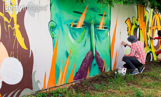 Side View Of Street Artists Painting Graffiti On Wall - gettyimageskorea