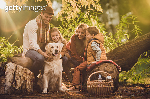 Young happy family enjoying with their dog on picnic in the park. - gettyimageskorea