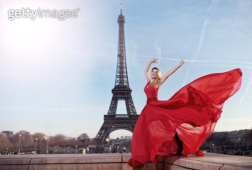 glamour shot of attractive blond hair woman with her dress in the wind posing with Eiffel Tower in background and feeling seductive. - gettyimageskorea