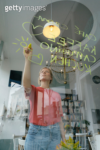 Young woman writing offer on windowpane in a cafe - gettyimageskorea