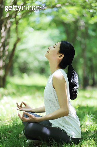 Young woman meditating in park - gettyimageskorea