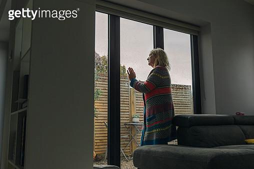 Senior woman looking through wet window - gettyimageskorea