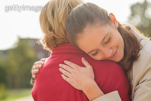 Granddaughter and her grandmother caressing each other - gettyimageskorea