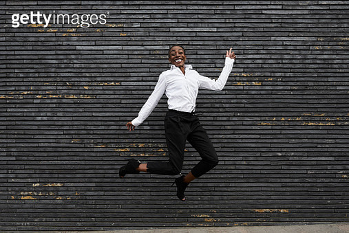 Grinning businesswoman jumpng in the air - gettyimageskorea