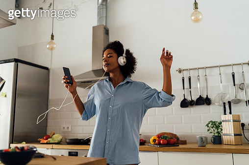Woman dancing and listening music in the morning in her kitchen - gettyimageskorea