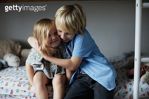 Happy smiling little boy giving his toddler sister a hug - gettyimageskorea