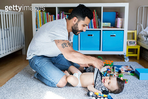 Father dressing up baby girl on carpet in bedroom - gettyimageskorea