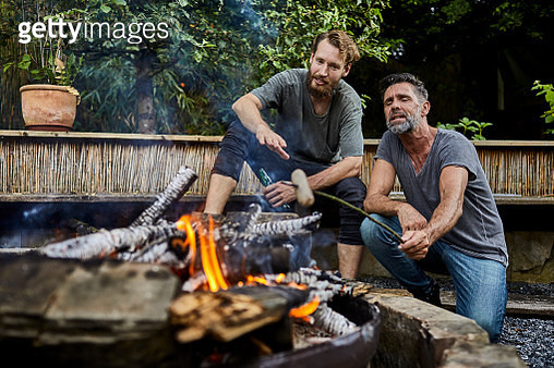 Friends sitting together at camp fire roasting sausages - gettyimageskorea