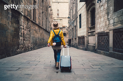 Young woman with suitcase walking at the street in Barcelona - gettyimageskorea