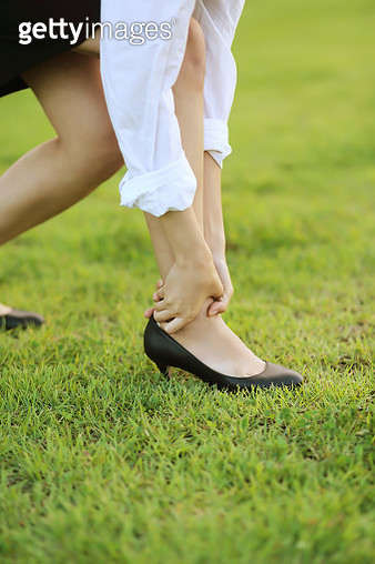 Businesswoman suffering from ankle pain outdoors - gettyimageskorea