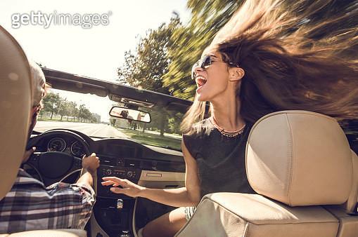 Cheerful woman having fun in cabriolet with her boyfriend. - gettyimageskorea