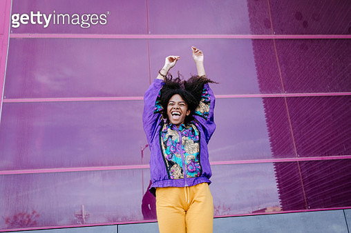 Young woman with urban look cheering in front of pink glass wall - gettyimageskorea