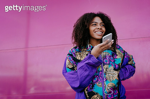 Smiling woman using hands-free phone, pink wall in the background - gettyimageskorea