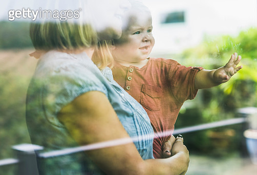 Mother looking out of window, with son on her arm - gettyimageskorea