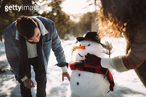 Young friends making snowman in the snow in winter - gettyimageskorea