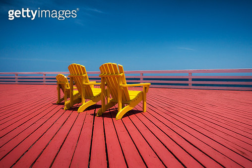 Three yellow chairs on red wooden decking - gettyimageskorea