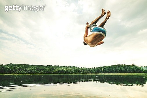 Full Length Rear View Of Shirtless Man Jumping Over River Against Sky - gettyimageskorea