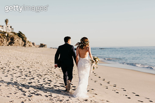 Rear view of happy bridal couple running at the beach - gettyimageskorea