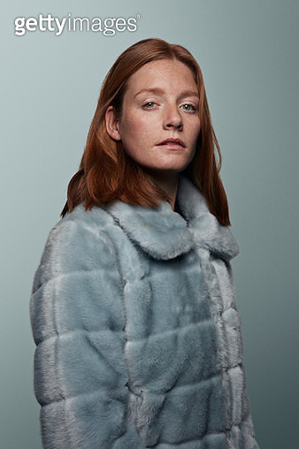 Young woman looking in camera, wearing artificial fur jacket - gettyimageskorea