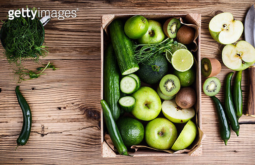 Fresh sliced green vegetables and fruits in wooden crate on rustic background viewed from above - gettyimageskorea
