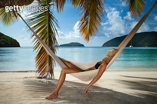 Woman relaxing in a hammock on a tropical beach, Maho Bay, St. John - gettyimageskorea