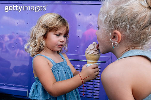 Happy pair of sisters sharing and licking ice cream cone - gettyimageskorea