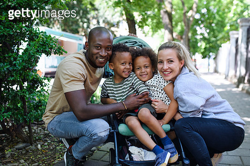 Portrait of family with two small children in park in city, looking at camera. - gettyimageskorea
