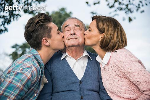 Grandson and daughter kissing senior mans cheek - gettyimageskorea