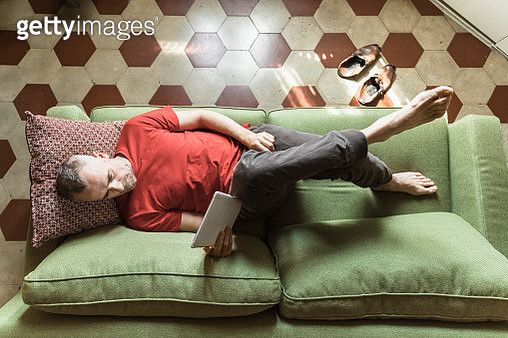 Mature man lying on sofa in living room and using tablet - gettyimageskorea