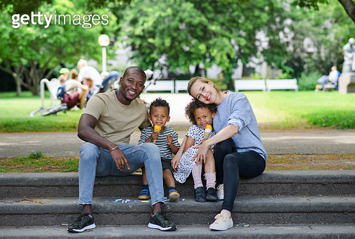 Portrait of family with two small children in park in city, eating ice cream. - gettyimageskorea