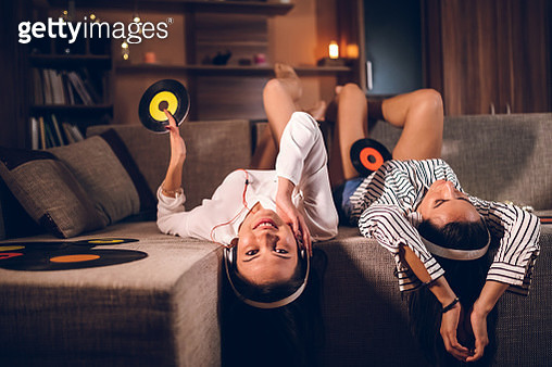 Two young females listening to old records, in the cozy atmosphere of their home. Laying upside down. - gettyimageskorea
