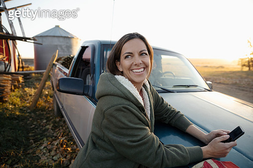 Smiling, happy female farmer using smart phone at pickup truck on farm - gettyimageskorea