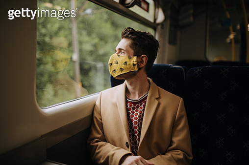 Train commuter wearing PPE face mask for safety - gettyimageskorea