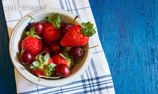 Ceramic bowl with strawberries and cherries over a dish cloth. Still life. - gettyimageskorea