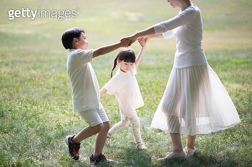 Mother and children dancing joyfully in park - gettyimageskorea