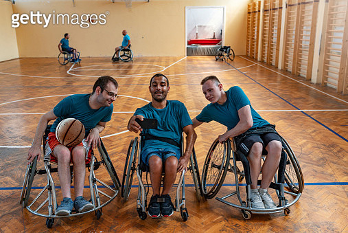 Group of smiling disabled basketball players on a wheelchair taking a selfie in a basketball court during the day. Photo of three handsome players men smiling and taking selfie while playing basketball at playground indoors during summer sunny day. Three  - gettyimageskorea