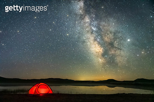 Camping outdoors by the lake, the Milky Way in the sky is clearly visible. - gettyimageskorea