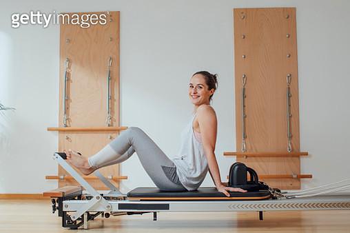 Portrait of beautiful Caucasian woman in sportswear sitting on pilates reformer. - gettyimageskorea