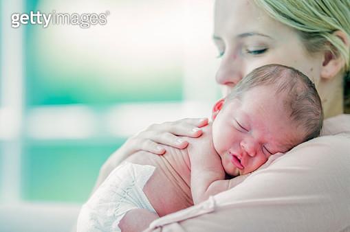 Newborn baby sleeping on mom's shoulder - gettyimageskorea