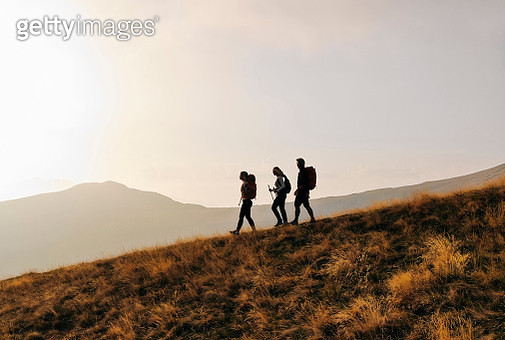 Hiking family follows alpine trail, on ridge crest - gettyimageskorea