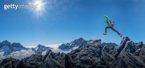 Side view of a  female climber jumping between two rocks on a mountain ridge in the Swiss Alps - gettyimageskorea