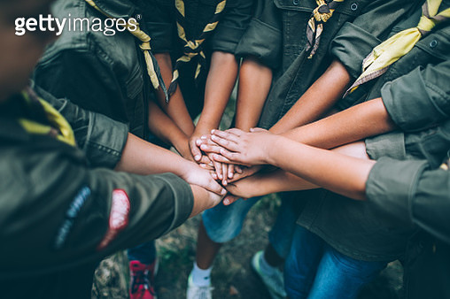 Group of young scouts joining hands together, showing their unity. - gettyimageskorea