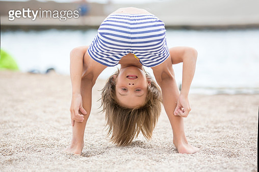 Child standing upside down on the beach, smiling happily while having fun on the sand - gettyimageskorea