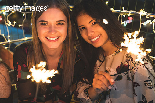 Female friends sitting at rooftop with sparklers - gettyimageskorea